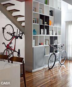 Como é muito alta, a estante (Indústria de Móveis Marvelar) precisou ter espessura de 40 cm para ficar estável. Os moradores adoram pedalar – daí a ideia de exibir as bicicletas na sala.