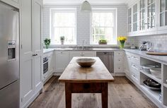 Beautiful white kitchen with rustic wood floors.