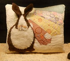 Appliqued bunny on an antique Grandmother's Fan quilt block. The bunny is made from layers of plush felt giving it depth and diminsion.
