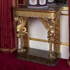 Bailey and Sanders; 1811. A pair of small rectangular console tables of gilt wood with rounded front corners, each with a rounded rectangular marble top. Carved and gilt frieze with blind fret work, the front legs carved as winged dragons resting on bird's claws. Back legs formed of flat gilt supports. On rectangular black marble base with brown veins.