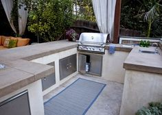 Beautiful elements of Art Deco landscape design - colored concrete countertops, stucco-covered cinderblock island, and stainless steel appliances. The blue color makes a great accent. Designed by Stout Landscape.