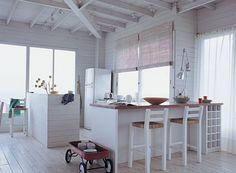 La barra principal de la cocina tiene una estructura para guardar botellas en uno de sus extremos. Está acompañada de banquetas altas y una ...