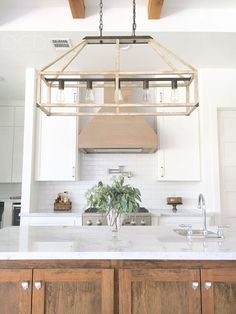"""The rustic lighting is """"Fredrick Ramond FR41205IRR Emilie 5 Light 42 inch Iron Rust Linear Chandelier Ceiling Light"""". The kitchen hood is White Oak with a Classic Grey stain. Backsplash is Bright White Ice Subway Ceramic Tile. Pot filler is by Danze Parma."""