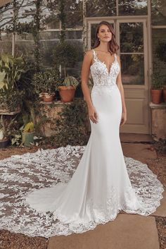 Look stunning on your wedding day in this fit and flare gown. Embroidered lace with sequins is paired with an illusion plunge to embellish the bodice. The back features a breathtaking cathedral length illusion train with an open back and thin straps. This gown is also available with a chapel length train.