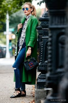 Olivia Palermo wears a printed blouse and a skinny scarf with skinny jeans, lace-up flats, a beaded handbag and a green coat.