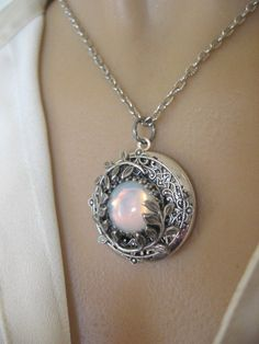 Moon Necklace, LOCKET, Silver Locket Necklace, Full Moon Pendant, Full Moon Necklace, Enchanted Moon.   This midnight stroll inspired locket necklace features a glowing white opalite jewel framed with lovely, leafy branches. The locket is covered with a filigree an elegant, antique effect. It opens to hold two photos or other of your favorite memorabilia. This is a lovely gift for someone special.   **Locket: 1.25 (30mm) in diameter **Chain: lobster claw closure **Stone: Quality Czech glass…