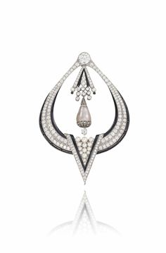 AN ART DECO DIAMOND, PEARL AND ONYX BROOCH -  Of open-work drop shaped design, the circular-cut diamond surmount suspending an articulated diamond, enamel and pearl tassel panel and further light brown natural pearl drop, hung within the graduated similarly-set frame, with black enamel and onyx border and central triangular shaped pearl cluster highlight, circa 1925