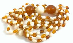 Beautiful suit necklace in cream and caramel featuring large focal beads. The perfect gift for her this holiday season. Great for boho mod