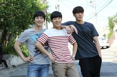 """The film """"Twenty"""" released stills that show off the chemistry between lead actors Kim Woo Bin, Kang Ha Neul, and 2PM's Junho. The two stills from the film portray an easy and comfortable friendship between the three leads. In one photo, the three men are wearing casual clothes, with their arms aroun..."""