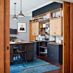 A vibrant blue and turquoise rug shines agains the wood and black details of the room while complimenting the powder blue shade of the walls. Painted black drawers add additional storage above and below the untreated wood cabinets for a strip-like effect. A metal framed book shelf fits perfectly within the cabinet set up and matched the industrial, metal desk.