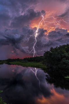 Dark storm clouds are highlighted by the pink sunset, illuminating the staggering lightning!