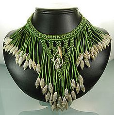 bib necklace made from soft green silk cord, small shells, and one centered cross sectioned shell