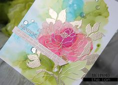 Stamp The Ton's Dearest Peony on  glossy cardstock using Vanilla Frosted Cupcake as my guide.  I sprayed rubbing alcohol on the glossy cardstock then dripped Aqua, Pool, Limeade, Citrus alcohol inks and blew them to the direction I wanted, avoiding the flower.  I then applied my pink alcohol inks (Raspberry, Flamingo, Shell Pink) on the peony. After the panel was dry, I heat embossed the image in Liquid Platinum using the MISTI