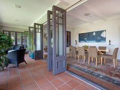 Bi-fold doors sliding back onto a tiled verandah #doors