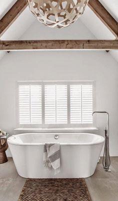 Een modern #vrijstaand #bad in een lichte grote ruimte met als raamdecoratie #shutters. Het oude balkenplafond is behouden!