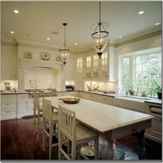 This white kitchen has great design: nice big window, beautiful range and vent, large  and open wood island, elegant yet simple glass globe lighting, and lighted glass  door cabinets.