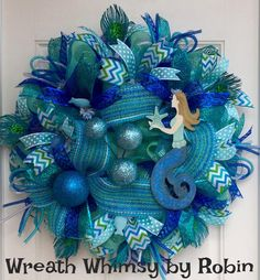Under The Sea Deco Mesh Mermaid Wreath.  All the shades of the sea are represented in this beautiful wreath. Perfect for the beach house or all summer long.  This wreath is constructed with 4 different colors/types of deco mesh giving it a true flavor of the ocean. The base is done in a sparkling aqua then ruffles of royal blue and turquoise foil are layered on top. A beautiful woven paper mesh is then woven throughout. Attached to the wreath are 36 ribbon streamers including; chevron, polka…