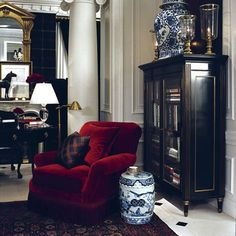 Ralph Lauren A lovely room Ralph Lauren room with a plush red velvet club chair, ebonized cabinet, and touches of brass. The blue and white Chinese garden stool is a perfect choice, but my favorite pi