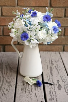 white sweet pea, white fresia, light blue tweedia, light blue hydrangea, white mini calla and bright blue cornflower