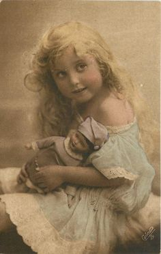 girl sits with doll on lap, facing left, looks front & up