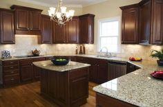 countertops for dark kitchen cabinets using giallo ornamental granite below antique steel chandelier with uplight lamp shade alongside single hung window tracks