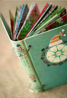 I LOVE this idea.... use a old book cover collect christmas card's or fit it with Christmas pictures of family.