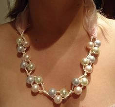 Making A Necklace By Stringing Three Pearls in Clusters....Summary: Making a necklace by tying three colored pearls in clusters with ribbon. Go on tying ribbon with pearls until your necklace is long enough. Then cut a short organza ribbon as the other part of necklace.