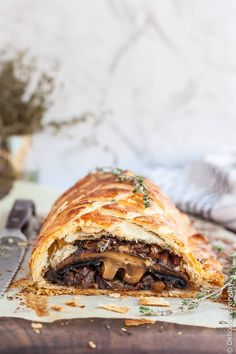 Vegan Mushroom Wellington - portobello mushrooms are encased in flakey golden pastry surrounded by baby spinach and caramelised onions
