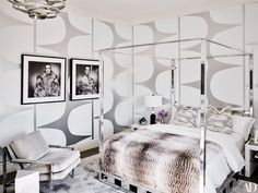 A vintage Milo Baughman four-poster and chair add to the monochrome aesthetic of a guest bedroom. On bed, Frette linens; vintage photographs of Kris Jenner.