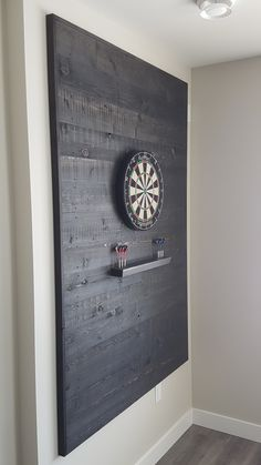 Dart board backer Custom backer for dart board. Rustic cedar boards stained dark gives this a warm and inviting feel. Great addition to any games room or man cave! Garage Game Rooms, Game Room Basement, Man Cave Garage, Man Cave Basement, Rustic Basement, Garage Bar, Cozy Basement, Garage Ideas, Game Room Bar
