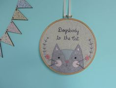 Cat hoop art, an ideal funny gift for the crazy cat lady in your life. Its hand embroidered phrase Dogsbody to the Cat makes it the perfect funny gift for a cat lover, looking for some apt cat wall art.  This cat embroidery hoop wall hanging, is a 7 inch embroidery hoop art piece and features a hand-cut and stitched wool-blend felt cat, complete with 3D whiskers. Roses and leaves in pretty shades of pink and grey are meticulously hand-stitched to help frame our felt feline friend…
