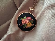 Flower embroidered handmade necklace. The design of this product is mine and totally unique. This necklace features hand embroidered flowers in shades of pink, burgundy,coral and green on a black cotton fabric.  Necklace frame color: copper Necklace diameter: 30 mm Chain length : 62 cm