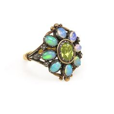 An opal and peridot cluster ring featuring an oval peridot center in a surround of opals decorated with scrollwork and rose diamond accents, to the openwork shoulders, in silver and 18k gold.  Portugal. circa 1940 - http://www.kentshire.com/