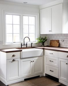simple classic country cottage kitchen with white cabinetry and timber benchtops, white subway
