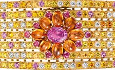 Boucheron close up of the Isola Bella watch bracelet, set with a pink oval sapphire and pink and orange cabochon sapphires, paved with yellow, pink and orange sapphires, emeralds and diamonds, on yellow gold. A watch is hidden under the central pattern.