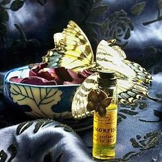"""A perfume by Villainess Soaps based on the heroine of the Blud e-novella. Sparkling wings and bubbles of anticipation. Sheer blue musk and a breath of old books, delicate touches of blackberry and juniper, and a whisper of plumeria."""". A gauzy, sheer, 6ml Extrait, accented with a signature bronze butterfly."""