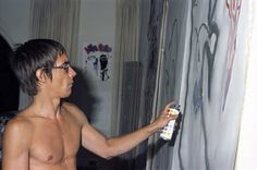 Iggy Pop does some interior decorating in his rented Malibu beach house, 1977.