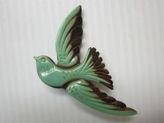 Beautiful carved patina green and brown c. 1940s bird brooch.