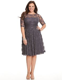 Luna lace dress by Kiyonna flatters every figure in sexy stretch lace with a shirred sash and an A-line skirt to play up hourglass curves. The flirty illusion neckline is backed with nude mesh to camouflage bra straps, with sheer elbow length sleeves. lanebryant.com