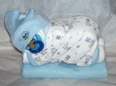 Diaper Baby - made out of rolled up diapers, a baby blanket, baby hat, pacifier and a baby Onesie. Find directions on You tube type in: How to make a diaper baby - Sleeping Baby Girl (Diaper Cake)