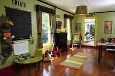 creative, fun playroom. love the colors, the black crown molding with the yellow trim, the framed (or painted border)  around the chalk board,and the decor is fun and  i love the letter words on the wall...