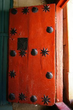 Church door with shells and stars. Now shells are for Santiago Saint James and I wonder whether the stars also represent the 'field of stars' at Compostela. But it's the colour that got me. What fantastic bright paint. Old Doors, Windows And Doors, Bright Paintings, Famous Castles, Unique Doors, Door Knockers, Closed Doors, Doorway, Gate