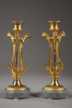 A pair of small tripod candlesticks composed of three incurvated pilasters decorated with foliage and griffin heads topped by the polished socket. Each bougeoir rests on a foot chiselled wit