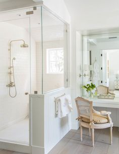 Crisp and bright white bathroom with glass shower and gold hardware