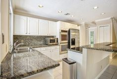 oven & fridge Traditional Kitchen with Crown molding, Kitchen island, limestone tile floors, Raised panel, High ceiling, Complex Granite
