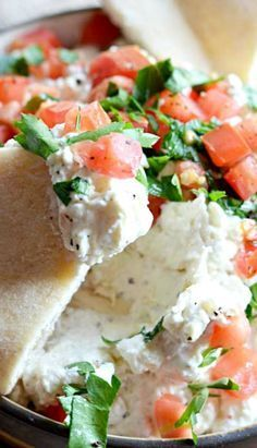 Garlicky Feta Dip 6 oz feta cheese, crumbled 4 oz cream cheese, softened ⅓ cup greek yogurt 2-3 cloves garlic, minced Pinch of dried dill Pinch of dried oregano 1 tablespoon lemon juice 1 Roma tomato, diced Chopped parsley, to garnish Black pepper, to taste Pita, chips, or crackers, to serve