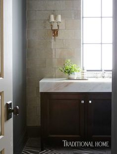 Ann Sacks tile adds subtle shimmer to the powder room walls. The veining of an onyx countertop draws on the dark tones of the vanity finish. - Photo: David A. Land / Design: Andrew Howard