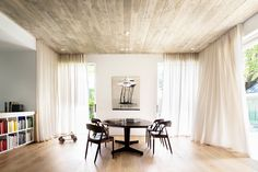 Downstairs, sheer curtains provide privacy and soften the large family room, while a concrete ceiling, traditionally framed by recycled hardwood timber contrast with a Porters oak floor. © Justin Alexander