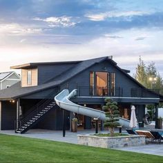 An incredible dark exterior on this pool house that was once a barn! This amazing transformation by Raykon Construction brings fun pool life complete with a slide and extra bedrooms for this family. Metal Building Homes, Building A House, Barn Pool, Pool Barn House, Modern Pool House, Modern Houses, Pool House Designs, Moderne Pools, Black House Exterior