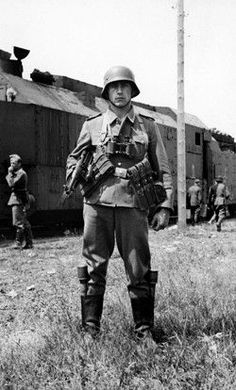A fully armed soldier posing in front of a armored Panzerzug train during 1940 - 1941